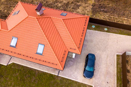 Aerial top view of house metal shingle roof with attic windows and black car on paved yard.