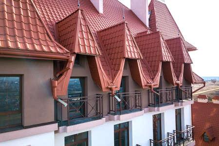 Close-up of building facade exterior with stucco wall, cast iron balcony railings, steep shingle roof and shiny windows.