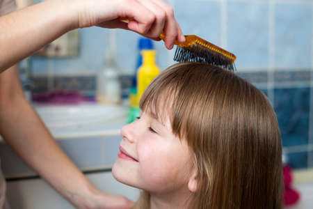 Mother hand with brush combing long fair hair of cute child girl after bath on blurred interior background.