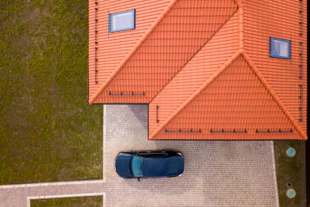 Aerial top view of house metal shingle roof with attic windows and black car on paved yard. Stock Photo - 121486382