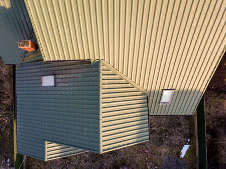 Aerial top view of green shingled house roof with new small attic plastic window.