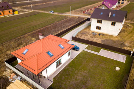 Aerial top view of house with metal shingle roof, brick chimneys and attic windows. Stock Photo