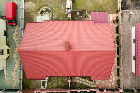 Aerial top view of house metal shingle roof on fenced yard background. Roofing, repair and renovation work.