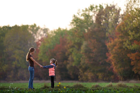 Back view of young slim attractive mother and child girl standing in green meadow holding hands outdoors on forest trees blurred background.
