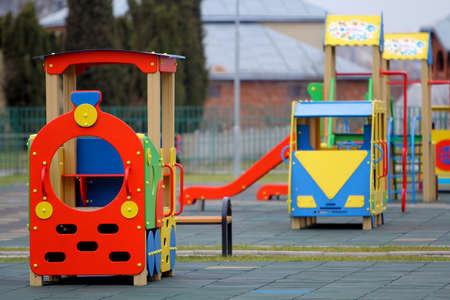 Bright colorful big toy cars on nursery playground with soft rubber flooring on bright sunny summer day. Perfect place for children activities and recreation outdoors.
