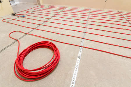 Heating red electrical cable wire roll on cement floor copy space background. Renovation and construction, comfortable warm home concept.