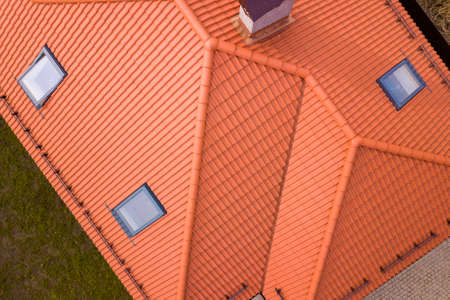 Aerial top view of house metal shingle roof, brick chimneys and small plastic attic windows. Roofing, repair and renovation work. Stock Photo