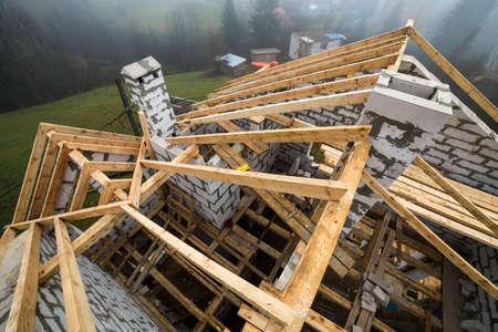 Top view of roof frame from wooden lumber beams and planks on walls made of hollow foam insulation blocks. Building, roofing, construction and renovation concept. 스톡 콘텐츠