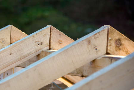 Close-up detail of roof frame of rough wooden lumber beams on background of misty mountain landscape in ecological area. Building, roofing, construction and renovation concept.
