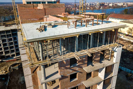Apartment or office tall building under construction, top view. Brick walls, scaffolding and concrete support pillars. Tower crane on bright blue sky copy space background. Drone aerial photography.