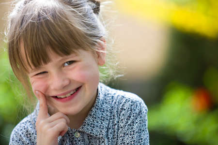 Cute pretty child girl with gray eyes and fair hair smiling in camera outdoors on blurred sunny green and yellow bright bokeh background.