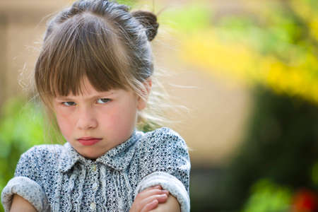Pretty funny moody young child girl outdoor feeling angry and unsatisfied on blurred summer green background. Children tantrum concept. Stock Photo