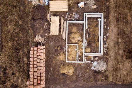 Concrete foundation for basement of future house, stacks of bricks and building timber logs for construction on sunny summer day, aerial view.