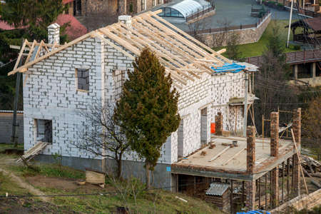 Two-storied cottage under construction. Walls of hollow foam insulation blocksand with window openings,roof beams frame and high chimneys, roofing underlayment. Imagens