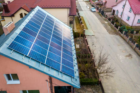 Close-up surface of lit by sun blue shiny solar photo voltaic panels system on building roof. Renewable ecological green energy production concept. Imagens
