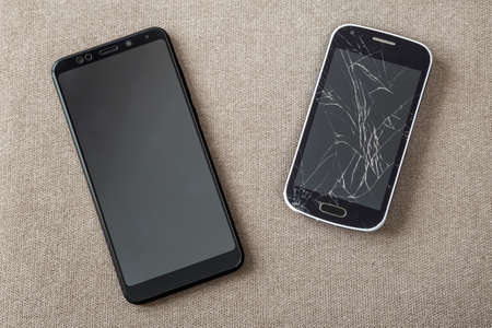 Comparison of two black mobile phones, old cellphone with cracked screen and new modern on light cloth copy space background. Technology progress and replacement concept.