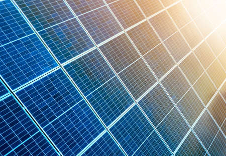 Close-up surface of lit by sun blue shiny solar photo voltaic panels. System producing renewable clean energy. Renewable ecological green energy production concept. Imagens