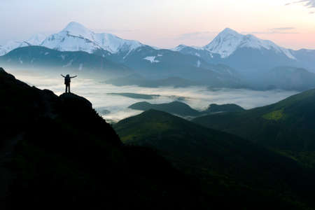 Wide mountain panorama. Small silhouette of tourist with backpack on rocky mountain slope with raised hands over valley covered with white puffy clouds. Beauty of nature, tourism and traveling concept Imagens