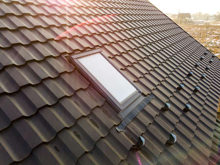 Close-up of new attic plastic window installed in shingled house roof. Professionally done building and construction work, roofing and installation concept. Imagens