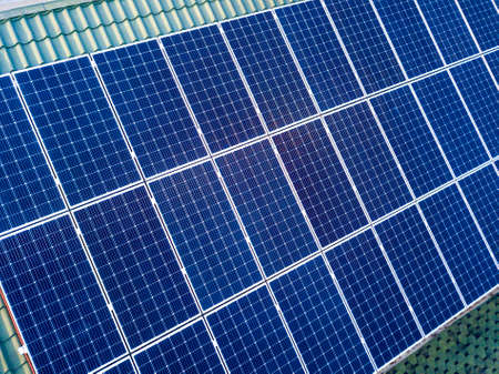 Close-up surface of blue shiny solar photo voltaic panels system on building roof. Renewable ecological green energy production concept. Imagens