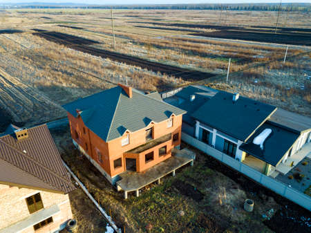 Aerial top view of two new residential houses cottages with shingle roof on fenced big yards on sunny day.