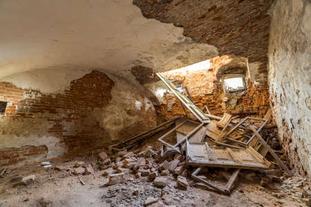 Old forsaken empty basement room of ancient building or palace with cracked plastered brick walls, low ceiling, small windows with and rubbish on dirty floor. 版權商用圖片