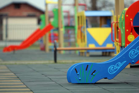 Bright colorful slides on nursery playground with soft rubber flooring on bright sunny summer day. Children activities and recreation outdoors.