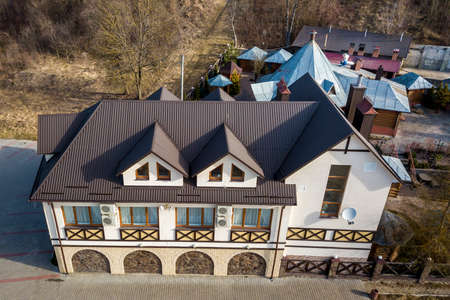 Aerial view of big house mansion complex on fenced property in ecological area on bright sunny day. Modern architecture, riches and luxury concept.