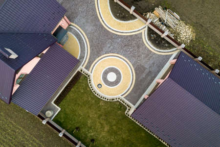 Aerial top view of house shingle roof on background of green lawn and colorful paved yard with geometrical abstract pattern. Roofing, repair and renovation work.