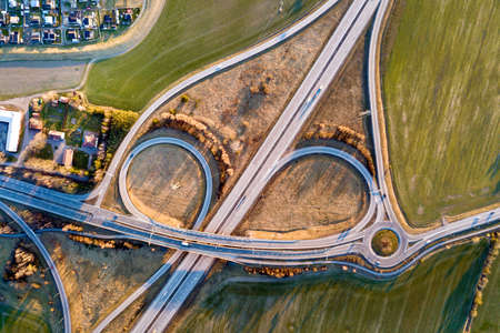 Aerial top view of modern highway road intersection, house roofs on spring green field background. Drone photography.