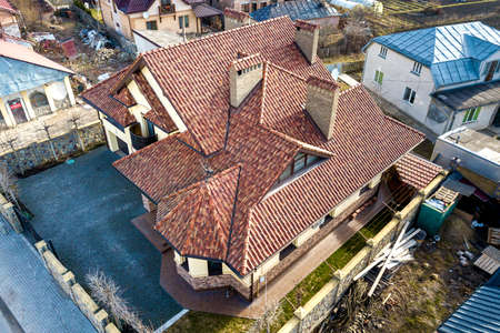 Aerial top view of complex house metal shingle roof and high brick chimneys. Roofing, construction, repair and renovation work. Stock Photo - 124552678