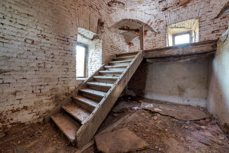 Large spacious forsaken empty basement room of ancient building or palace with cracked plastered brick walls, small windows, dirty floor and wooden staircase ladder. Stock Photo