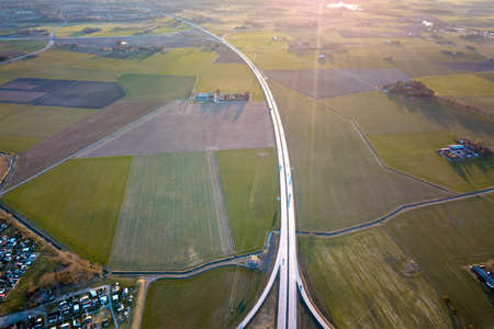 Aerial top view of rural landscape, modern highway road and small farm buildings on spring green field background. Drone photography. Reklamní fotografie