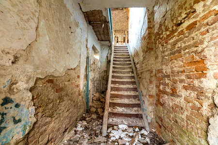 Large spacious forsaken empty basement passageway of ancient building or palace with cracked plastered brick walls and narrow steep wooden staircase ladder.