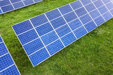 Surface of solar photo voltaic panels system producing renewable clean energy on green grass background.