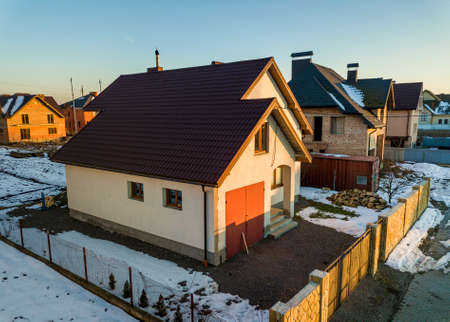 Aerial view of new residential house cottage and attached garage with shingle roof on fenced yard on sunny winter day in modern suburban area. Perfect investment in dream house. Stock Photo