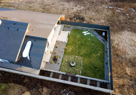 Aerial top view of new residential house cottage and terrace with shingle roof on fenced big yard on sunny winter day.