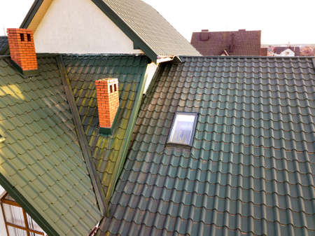 Green metal shingled house roof with attic plastic window and brick chimney. Stock Photo - 124550566
