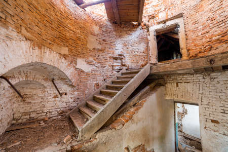 Large spacious forsaken empty basement room of ancient building or palace with cracked plastered brick walls, dirty floor and wooden staircase ladder. Standard-Bild