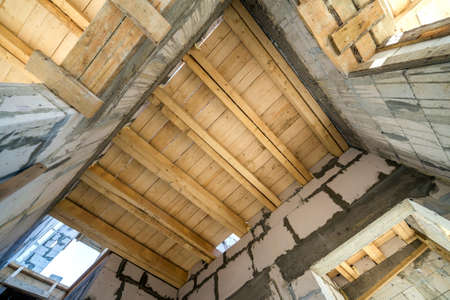 Close-up detail of house room interior under construction and renovation. Energy saving walls of hollow foam insulation blocks, wooden ceiling beams for roof frame. Zdjęcie Seryjne