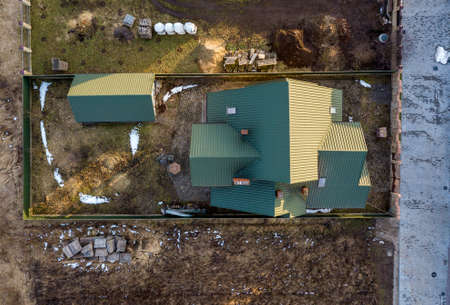 Aerial view of new residential house cottage and garage or barn with shingle roof on fenced yard on sunny day. Stock Photo