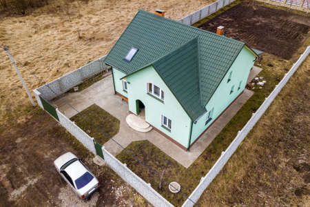 Aerial top view of new residential house cottage with brick chimney and attic window in shingle roof on fenced big property on sunny day.