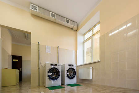 Modern new industrial washing machines on rubber insulation mats in clean light tiled bathroom or laundry room with air ventilation system.