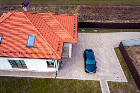 Aerial top view of house metal shingle roof with attic windows and black car on paved yard. Stock Photo - 124582823