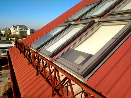 Red tiled house roof with attic windows. Roofing construction, window installation, modern architecture concept.