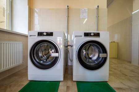 Modern new industrial washing machines in clean tiled bathroom or laundry room on rubber insulation mats.
