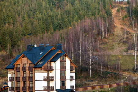 New modern comfortable four-story hotel building with attached premises, attic rooms and high chimneys in ecological rural area on spruce dense forest. Recreation and tourism concept.