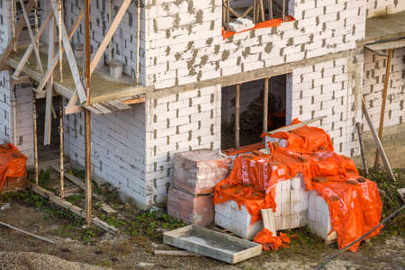 Building under construction. Roof beams frame and roofing underlayment, water-resistant waterproof barrier on walls of hollow foam insulation blocks. Masonry, roofing and renovation. Editorial