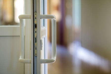 Wit kunststof deurdetail met metalen slot, handvat en transparant glas op een wazige interieurachtergrond. Installatie en ontwerpconcept. Stockfoto