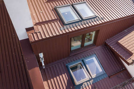 Aerial view of annex room exterior with plastic attic windows, roof and walls covered with brown metal decorative siding planks.